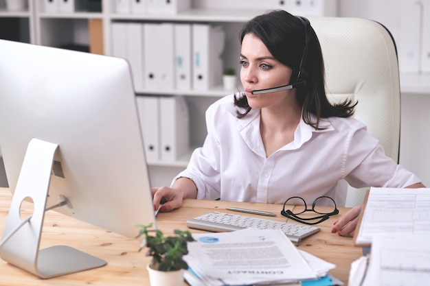 Concentrated female customer service operator sitting at desk and using computer while working with clients
