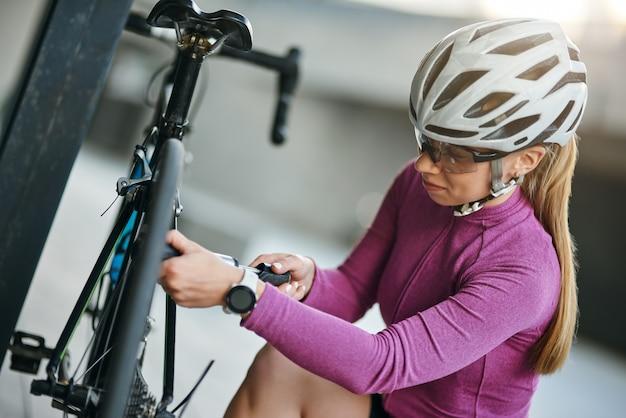 펌프를 사용하는 동안 집중적으로 보이는 보호 헬멧과 안경을 쓴 집중된 여성 자전거 타는 사람