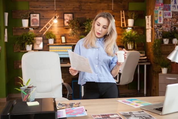 クリエイティブなデザインの紙を持っている集中女性デザイナー。