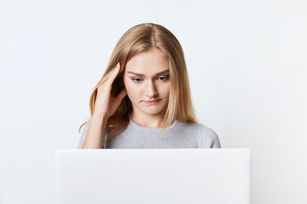 Concentrated female freelancer works at laptop computer.