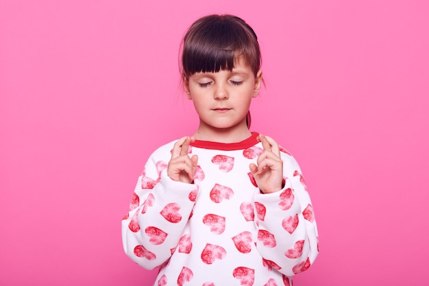 Concentrated female kid wearing casual jumper with hearts keeping eyes closed and fingers crossed, isolated over pink wall.