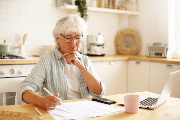 Concentrated female pensioner wearing eyeglasses focused on financial papers while paying bills online using laptop, holding pencil, making notes. people, technology, finances and domestic budget