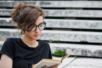 Concentrated female reading book on stairs