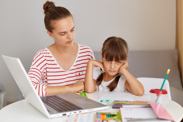Concentrated female sitting with her daughter schoolgirl at table with books and laptop, doing homework or having online lessons, mother helping her kid, distance education.
