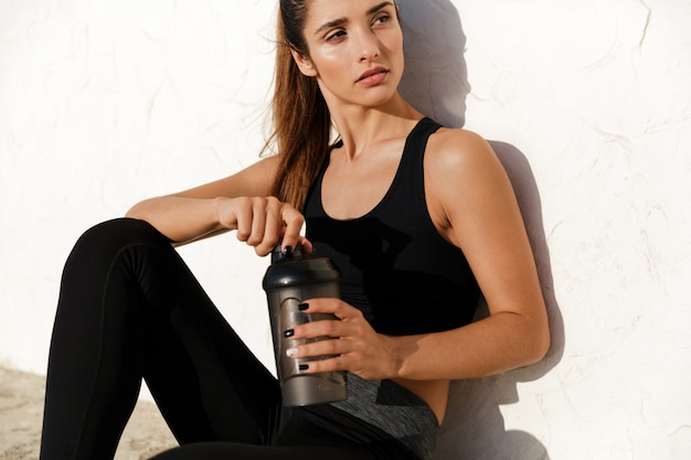 Concentrated fitness lady sitting outdoors drinking water.