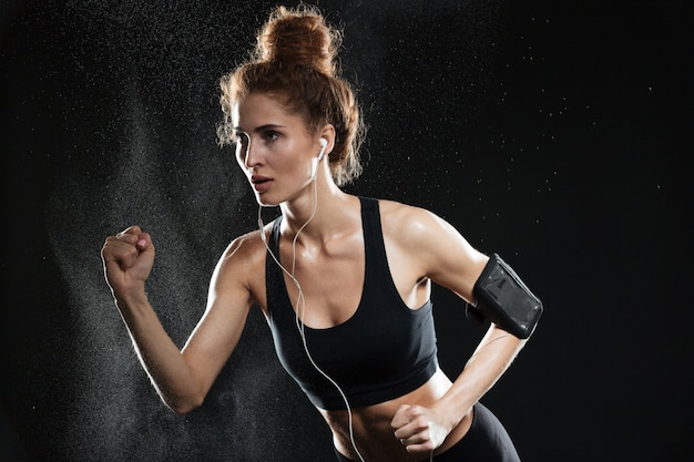 Concentrated fitness woman running in studio