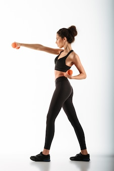 Concentrated fitness woman standing in profile and doing exercise with dumbbells