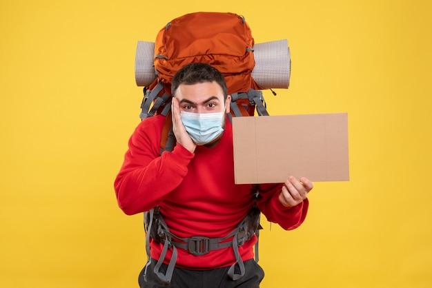 バックパック付きの医療用マスクを着用し、孤立した黄色の背景に何も書かずにシートを保持している集中力のある若い男