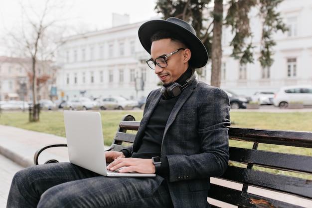 コンピューターと公園に座って帽子をかぶった集中フリーランスの労働者。自然のキーボードで入力するハンサムなアフリカの若い男の屋外写真。