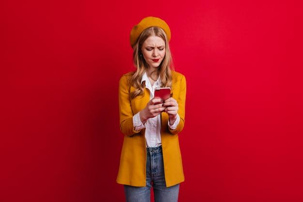 集中したフランスの女の子のテキストメッセージ。赤い壁にスマートフォンを使用してカジュアルな服を着た金髪の若い女性。