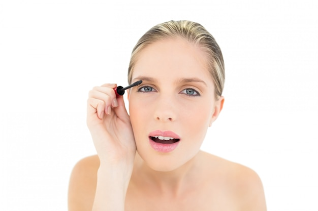 Concentrated fresh blonde woman applying mascara