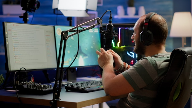 Concentrated gamer playing shooter game in gaming competition using wireless controller wearing professional headphones. online streaming cyber performing during tournament using rgb powerful pc