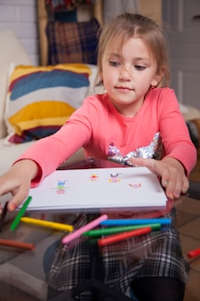 Концентрированная девушка, выбрав карандаш рисовать