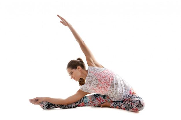 Концентрированные девушка делает упражнения гибкость