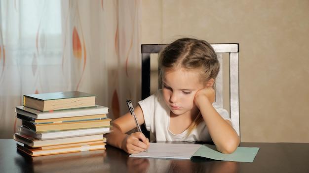 Концентрированная девочка делает домашнее задание в школе