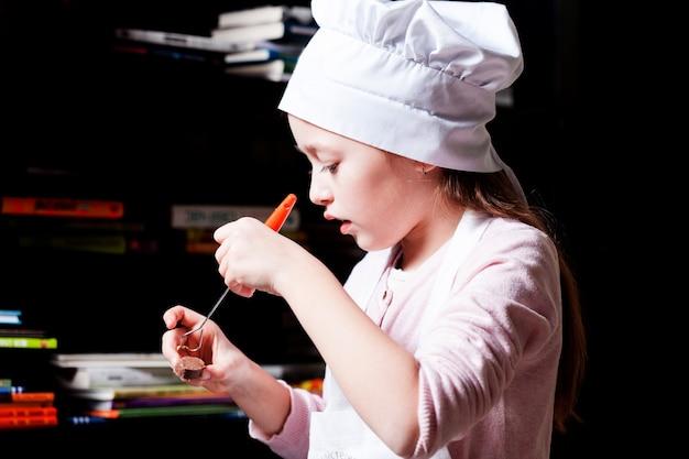 요리사 모자에 집중된 소녀는 초콜릿 사탕을 만듭니다. diy