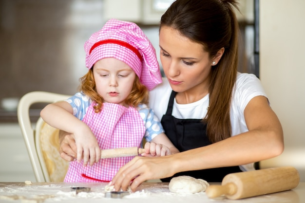 Concentrated girl kneading dough with young mother
