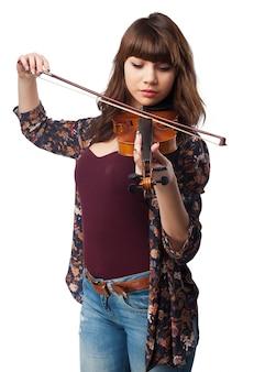 Концентрированные девочка играет на скрипке