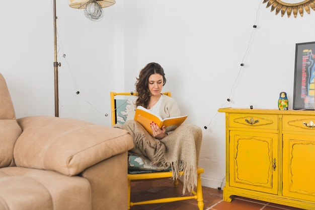 Concentrated girl reading a book sitting on a yellow chair