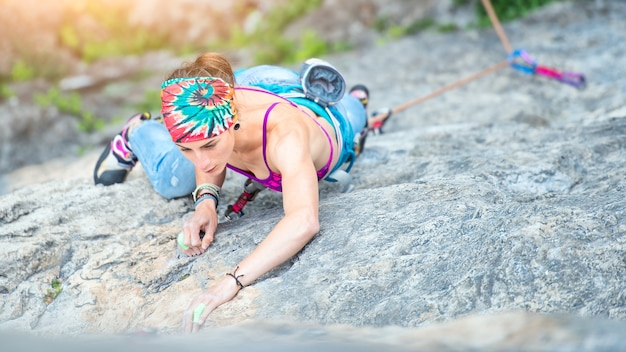 Concentrated girl in a rock climbing passage in summer