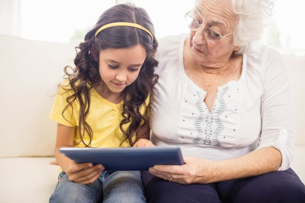 Concentrated granddaughter using tablet with grandmother at home