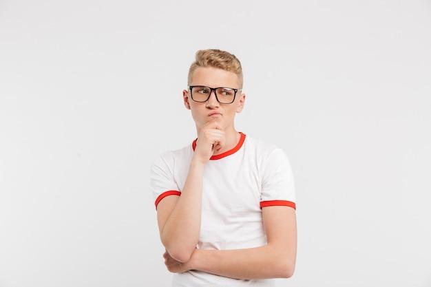 Сосредоточенный парень в очках смотрит в сторону с задумчивым взглядом и касаясь подбородка, изолированные на белом