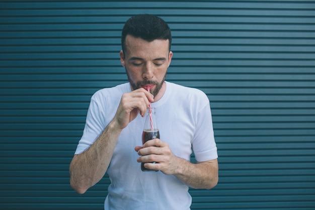 Концентрированный парень пьет кока-колу из бутылки через солому. он смотрит вниз. изолированные на полосатый