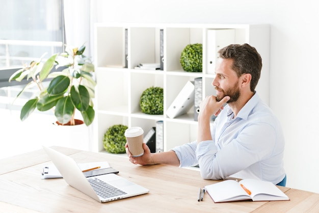 Сосредоточенный красивый бородатый мужчина держит кофе с помощью портативного компьютера.