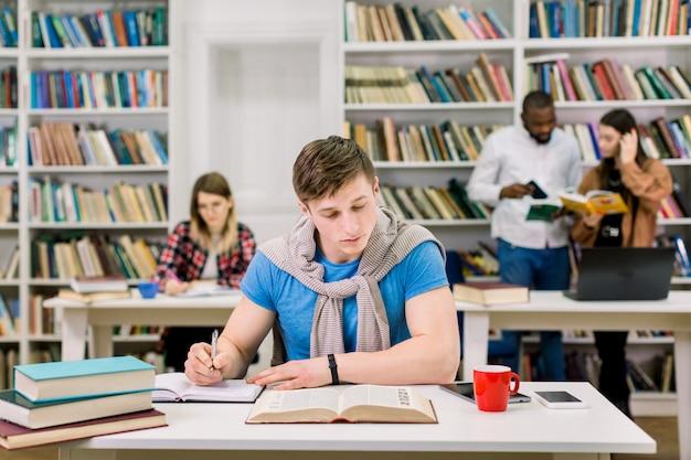 Сконцентрированный красивый парень изучает и пишет заметки из книги, сидит за столом в университетской библиотеке, готовится к экзаменам, пока его коллеги читают книги