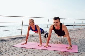 Concentrated handsome man and lovely girl doing push ups while training outdoors
