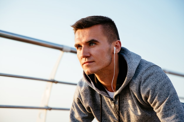 Concentrated handsome man in earphones listening to music during doing exercises