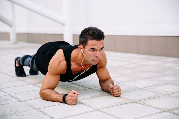 Concentrated handsome sportsman in earphones, doing push ups on elbows, working out