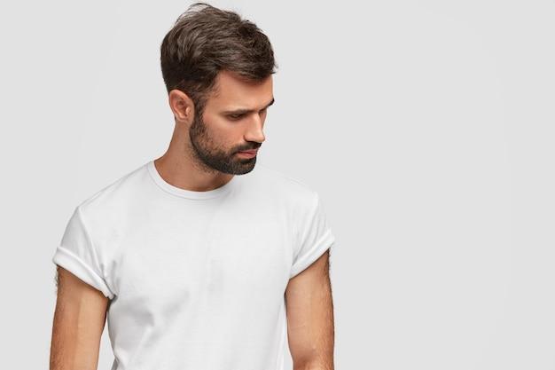 Bel giovane concentrato concentrato verso il basso, ha barba e capelli scuri, indossa una maglietta bianca casual