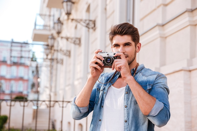 Concentrated handsome young man taking pistures with old photo camera in the city