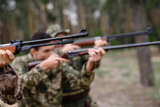 Concentrated hunters aiming with rifles bird hunt.