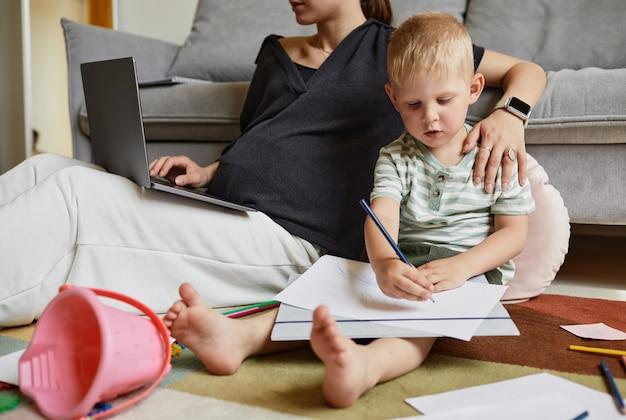 Сосредоточенный независимый маленький сын сидит на полу и рисует, пока его мать работает с ноутбуком