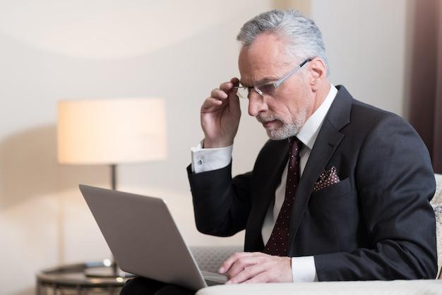 프로젝트를 진행하는 동안 노트북을 들고 호텔에 앉아 집중된 수염 사업가