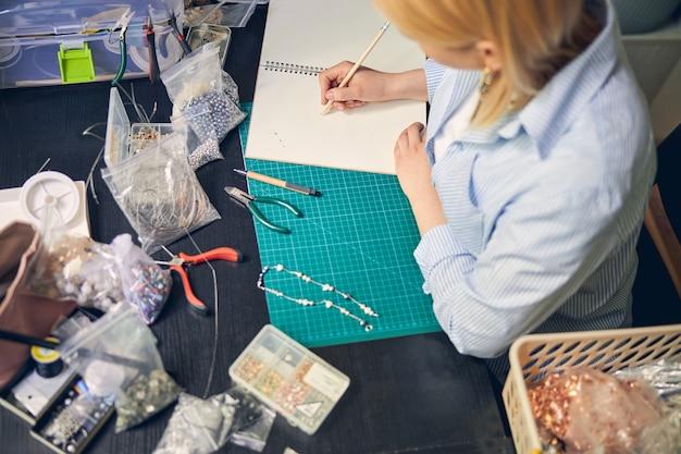 Концентрированный ювелирный мастер рисует эскиз жемчужного ожерелья.