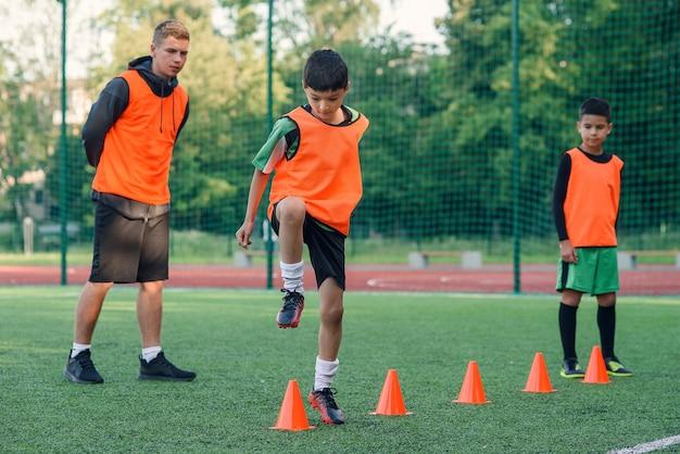 Сосредоточенный юный футболист, бегущий среди конусов