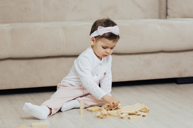 Сосредоточенный ребенок играет с деревянными кубиками