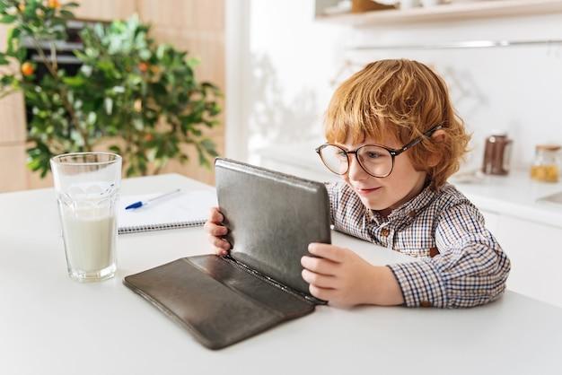 집중된 아이. 안경을 쓰고 부엌 테이블에 앉아있는 동안 그의 가제트를 들고 빨간 머리 똑똑한 좋은 소년