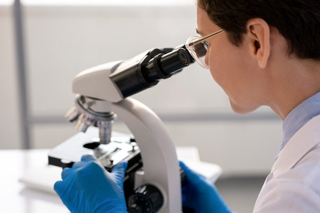 Concentrated laboratory worker in gloves using microscope while analyzing cell structure