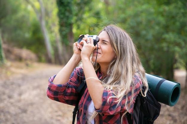 風景を撮影し、バックパックを持って歩く集中女性。自然を探索し、カメラを持って写真を撮る女性観光客。観光、冒険、夏休みのコンセプト