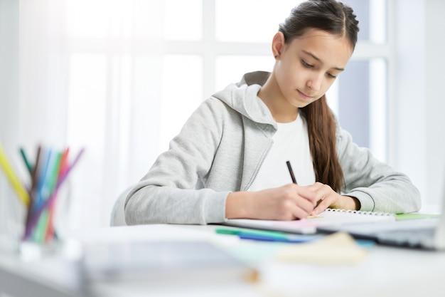 宿題をしながら、自宅のテーブルに座って、コピーブックにメモをとっている集中ラテン系の10代の少女。遠隔教育、ホームスクーリングの概念