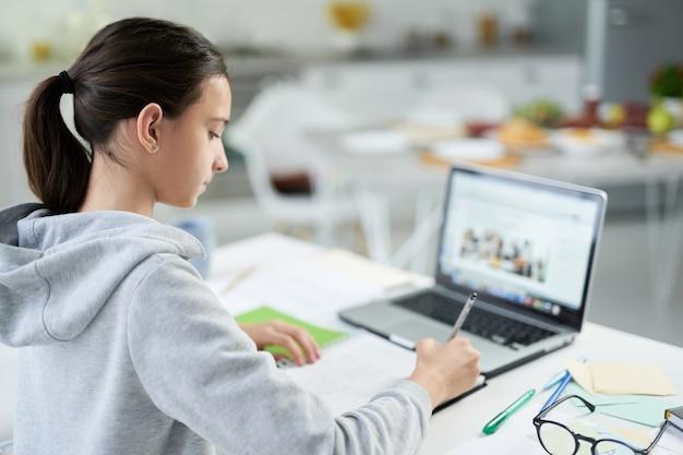宿題をしながら、ラップトップを使用して、自宅のテーブルに座ってコピーブックに書いている集中ラテン系の10代の少女。遠隔教育、ホームスクーリングの概念