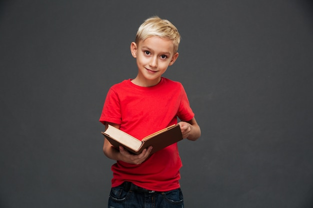 Concentrated little boy child holding book.