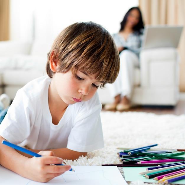 集中した少年の描画と彼の妹のチップを食べる