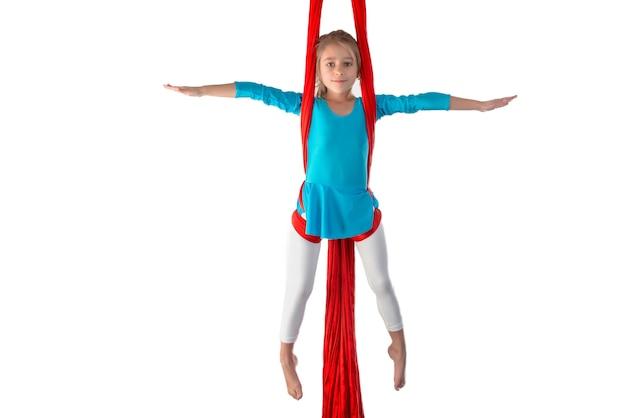 Сосредоточенная маленькая кавказская девочка в синем купальном костюме делает гимнастические упражнения на красной воздушной ленте на белом фоне. гимнастика на гибкость для детей. место для рекламы