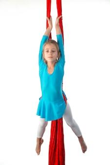 Сосредоточенная маленькая кавказская девочка в синем купальном костюме выполняет гимнастические упражнения на красной воздушной ленте