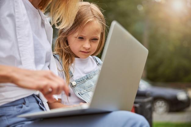 집중된 작은 여자 아이가 공원에 앉아 어머니와 함께 공부